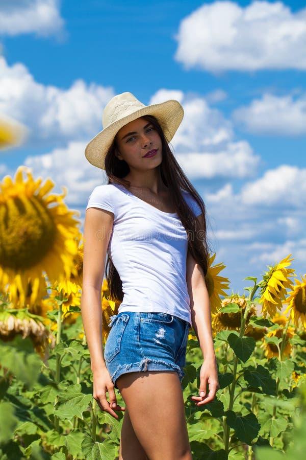 Portret van een jong mooi meisje op een gebied van zonnebloemen royalty-vrije stock afbeelding