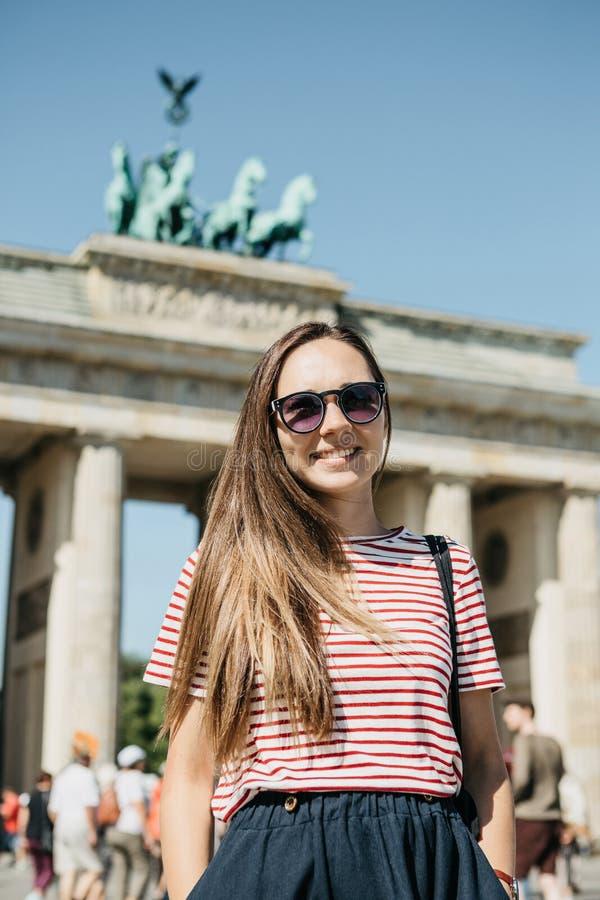 Portret van een jong mooi positief die modieus toeristenmeisje glimlachen stock foto