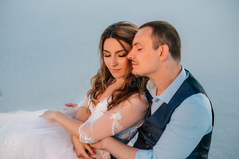 Portret van een jong paar Een man koestert zacht een vrouw Huwelijksfotografie, liefdeverhaal Wit zand als achtergrond bij zonson stock fotografie