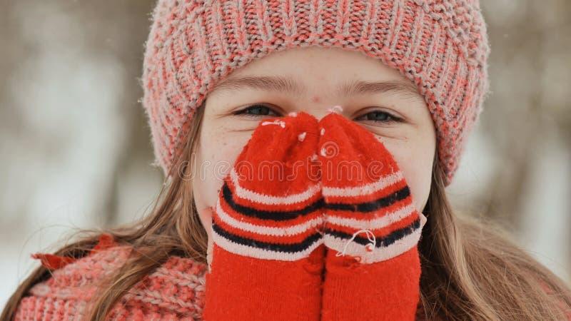 Portret van een jong schoolmeisje met sproeten in het hout in de winter Hij verwarmt van hem indient vuisthandschoenen en toepast royalty-vrije stock foto