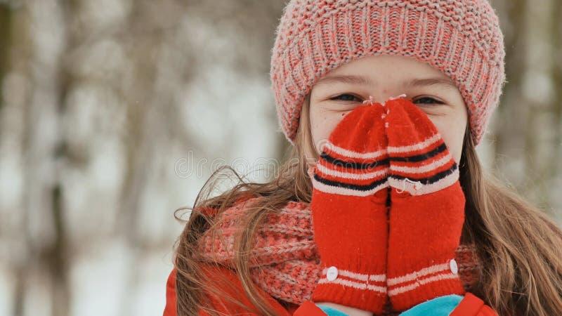 Portret van een jong schoolmeisje met sproeten in het hout in de winter Hij verwarmt van hem indient vuisthandschoenen en toepast stock fotografie