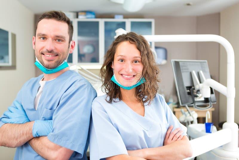 Portret van een jonge aantrekkelijke tandarts en zijn medewerker in van hem stock afbeelding