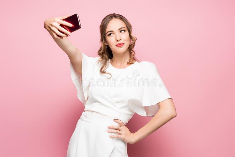 Portret van een jonge aantrekkelijke vrouw die selfie foto met smartphone op een roze achtergrond maken royalty-vrije stock afbeeldingen
