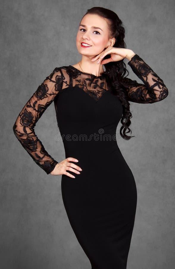 Portret van een jonge aantrekkelijke vrouw in een zwarte avondjurk royalty-vrije stock afbeelding