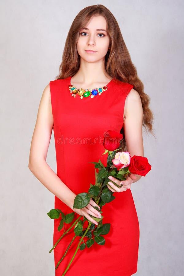 Portret van een jonge aantrekkelijke vrouw met een bos van rode rozen royalty-vrije stock afbeelding