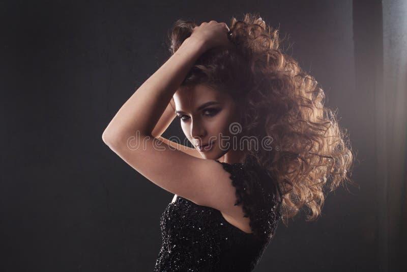 Portret van een jonge aantrekkelijke vrouw met schitterend krullend haar Aantrekkelijke brunette stock foto