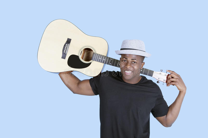 Portret van een jonge Afrikaanse Amerikaanse mensen dragende gitaar over lichtblauwe achtergrond royalty-vrije stock foto's
