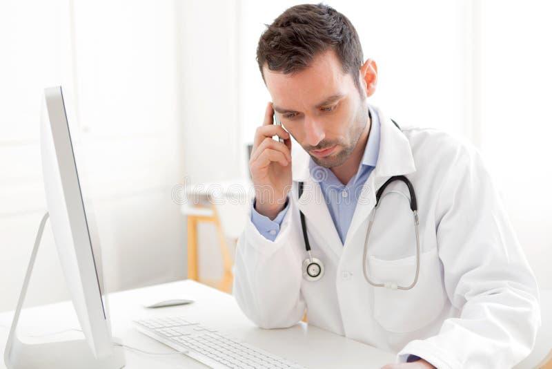 Portret van een jonge arts die een patiënt telefoneren stock foto's