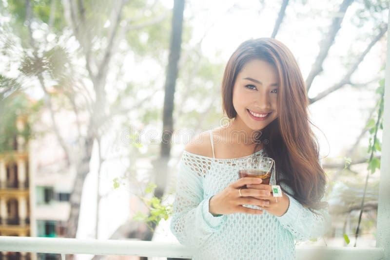 Portret van een jonge Aziatische vrouw die haar ochtendthee drinken Viel r stock afbeelding