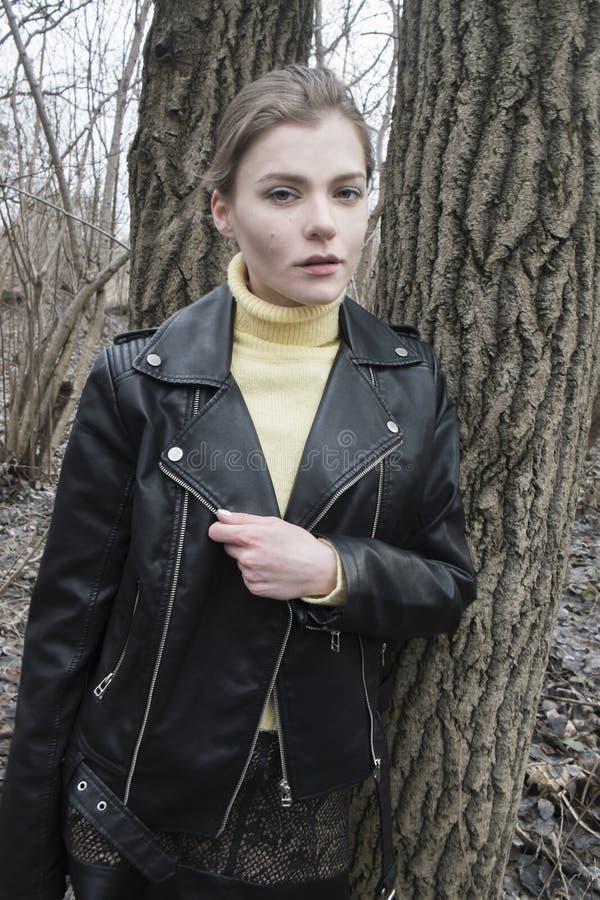 Portret van een jonge blonde vrouw in een zwart jasje in het hout stock foto's