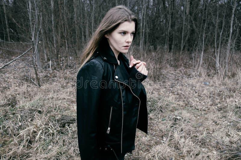 Portret van een jonge blonde vrouw in een zwart jasje in het hout stock fotografie