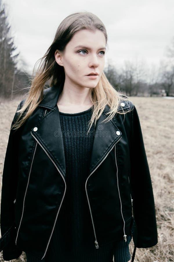Portret van een jonge blonde vrouw in een zwart jasje in het hout stock foto