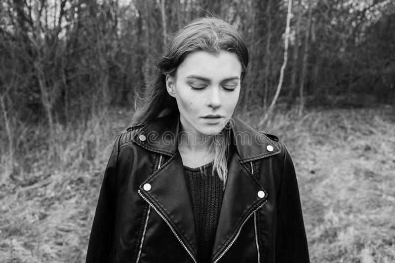Portret van een jonge blonde vrouw in een zwart jasje in het hout stock afbeeldingen