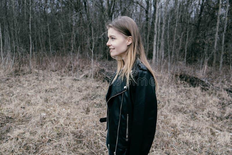Portret van een jonge blonde vrouw in een zwart jasje in het hout royalty-vrije stock afbeeldingen
