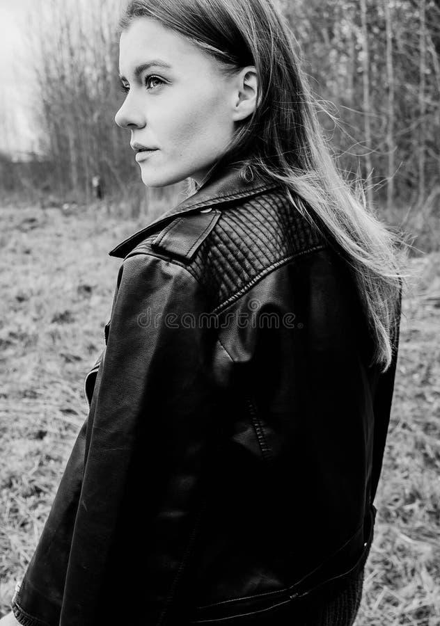 Portret van een jonge blonde vrouw in een zwart jasje in het hout royalty-vrije stock foto