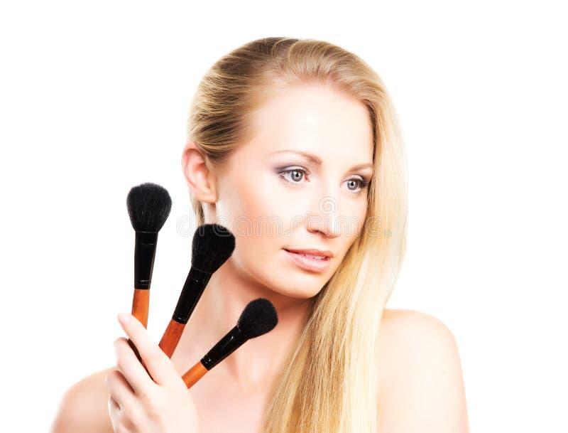 Portret van een jonge blonde vrouw met make-upborstels royalty-vrije stock foto's