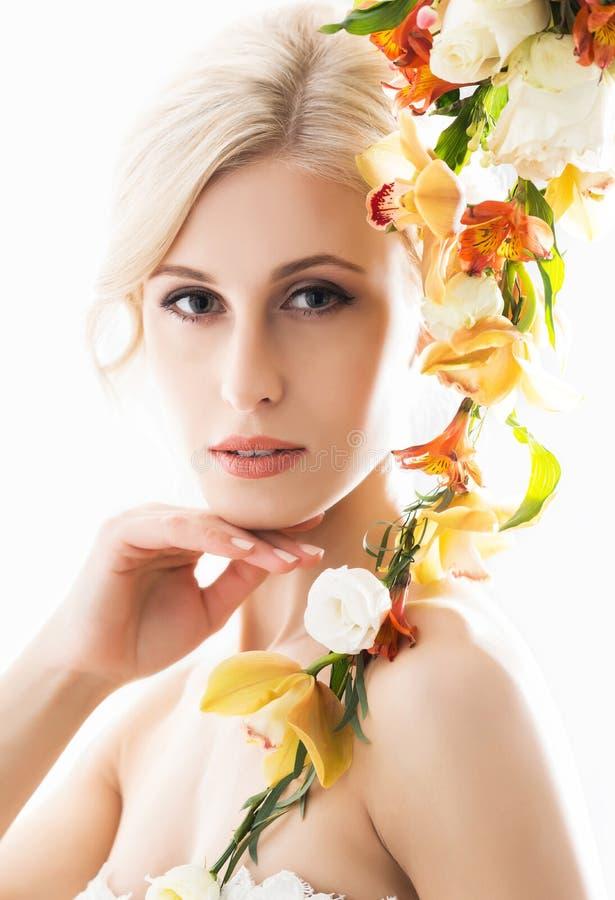 Portret van een jonge bruid in het witte kleding stellen met bloemen stock afbeelding