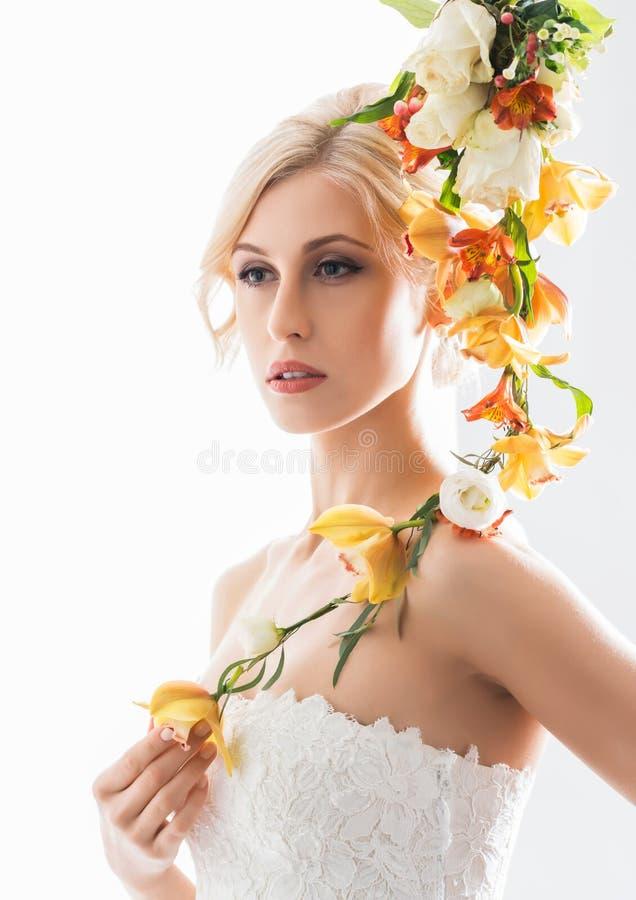 Portret van een jonge bruid in het witte kleding stellen met bloemen stock afbeeldingen