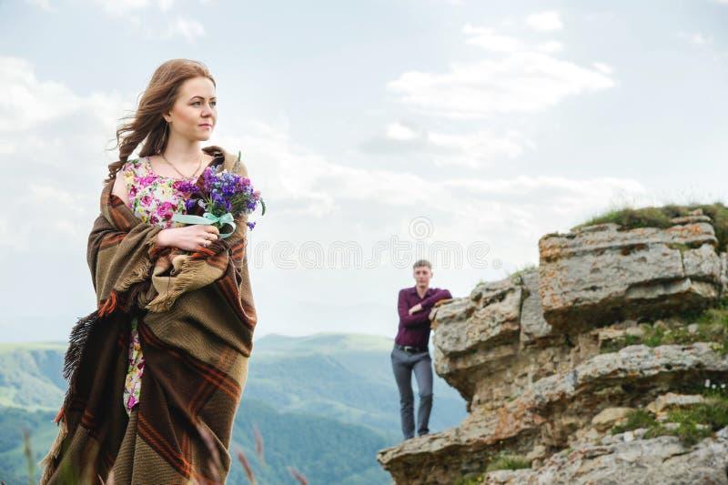 Portret van een jonge bruid in een kleurrijke kleding met een boeket van wildflowers in de aard die zich op de achtergrond bevind stock afbeeldingen