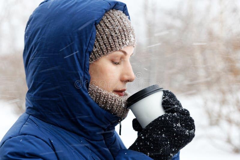 Portret van een jonge die vrouw door vliegende sneeuwvlokken wordt omringd stock foto