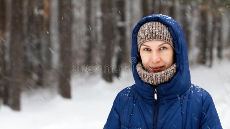 Portret van een jonge die vrouw door vliegende sneeuwvlokken wordt omringd stock afbeeldingen