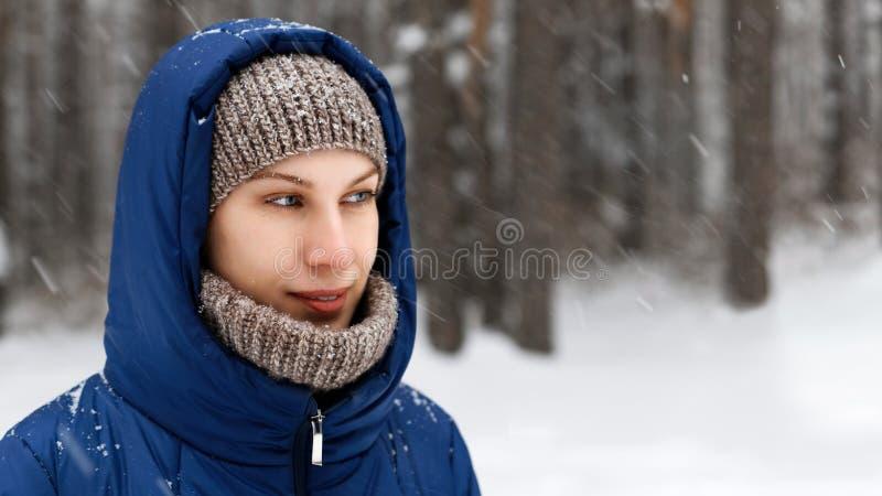 Portret van een jonge die vrouw door vliegende sneeuwvlokken wordt omringd royalty-vrije stock foto's