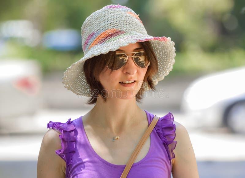 Portret van een jonge donkerbruine vrouw die hoed en zonnebril dragen stock foto