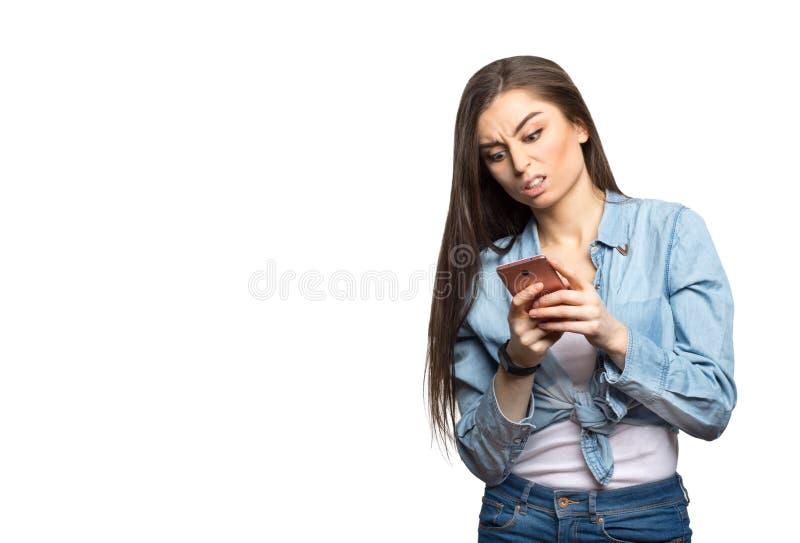 Portret van een jonge donkerbruine vrouw die smartphone in haar bekijken die handen boos en tegen witte geïsoleerde achtergrond w royalty-vrije stock foto