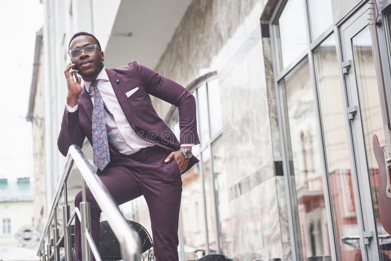 Portret van een jonge en knappe Afrikaanse Amerikaanse zakenman die in een kostuum over de telefoon spreken Het voorbereidingen t stock fotografie