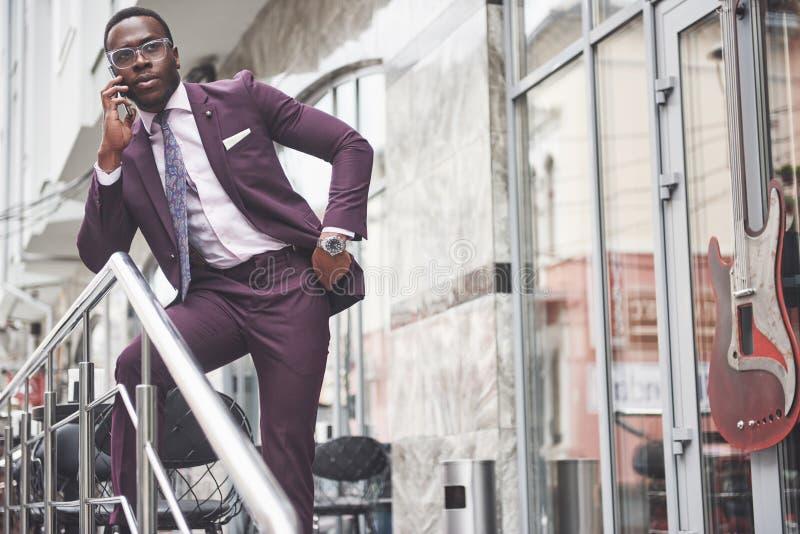 Portret van een jonge en knappe Afrikaanse Amerikaanse zakenman die in een kostuum over de telefoon spreken Het voorbereidingen t royalty-vrije stock foto