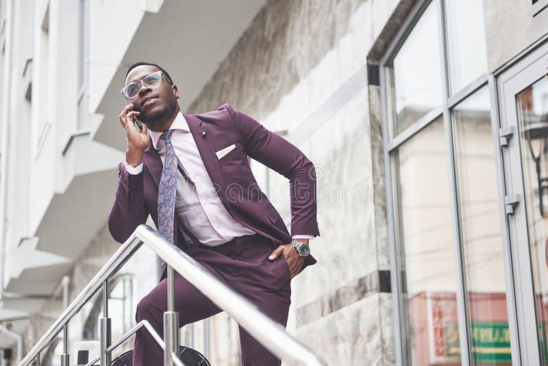 Portret van een jonge en knappe Afrikaanse Amerikaanse zakenman die in een kostuum over de telefoon spreken Het voorbereidingen t stock afbeeldingen