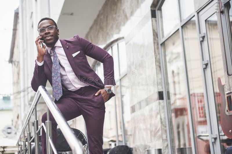 Portret van een jonge en knappe Afrikaanse Amerikaanse zakenman die in een kostuum over de telefoon spreken Het voorbereidingen t royalty-vrije stock fotografie