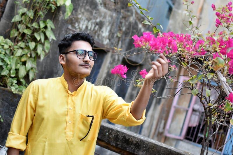 Portret van een jonge en knappe Indische Bengaalse mens die zich voor een uitstekend huis bevinden die groene Indische traditione royalty-vrije stock afbeeldingen