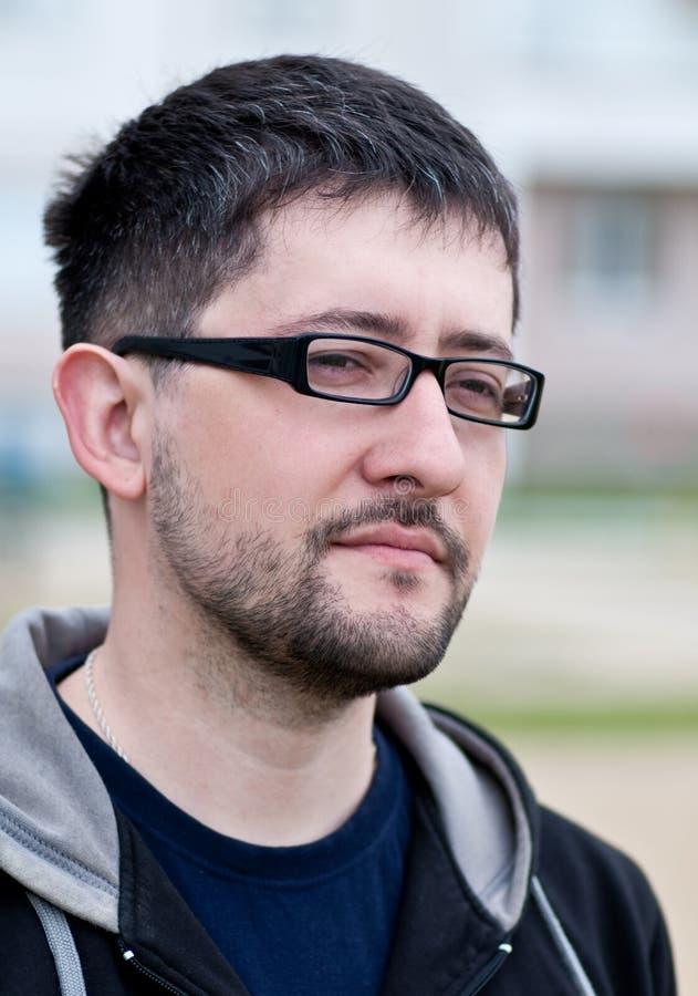 Portret van een jonge gebaarde mens die glazen draagt royalty-vrije stock foto's