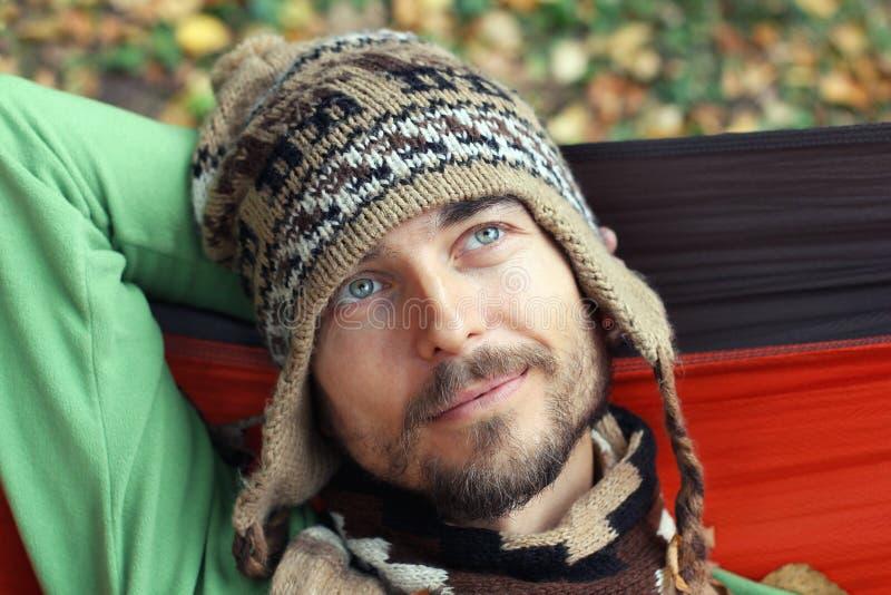 Portret van een jonge gebaarde mens in hoed en sjaal Hij is binnen rust stock afbeelding