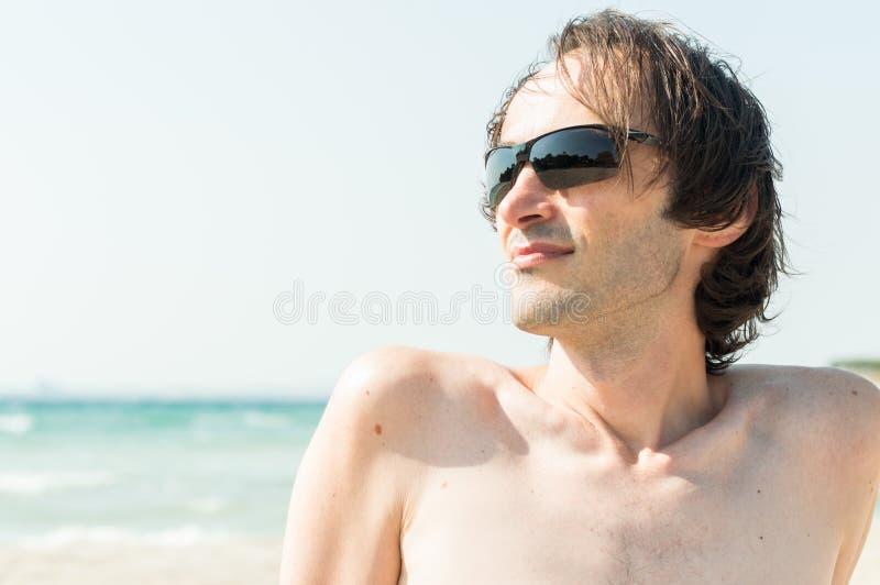 Portret van een jonge gelukkige Kaukasische mens die met zonnebril van de zon op het strand genieten royalty-vrije stock afbeeldingen