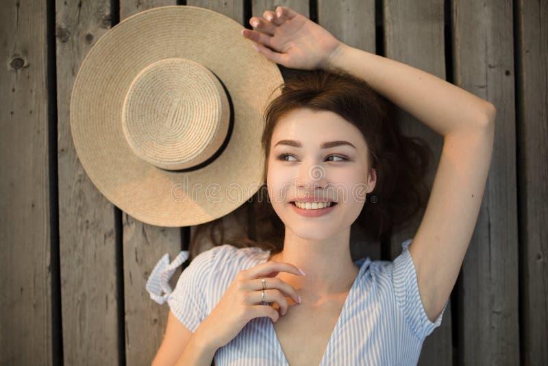 Portret van een jonge gelukkige vrouw Mening van hierboven Het liggen op houten achtergrond royalty-vrije stock afbeeldingen