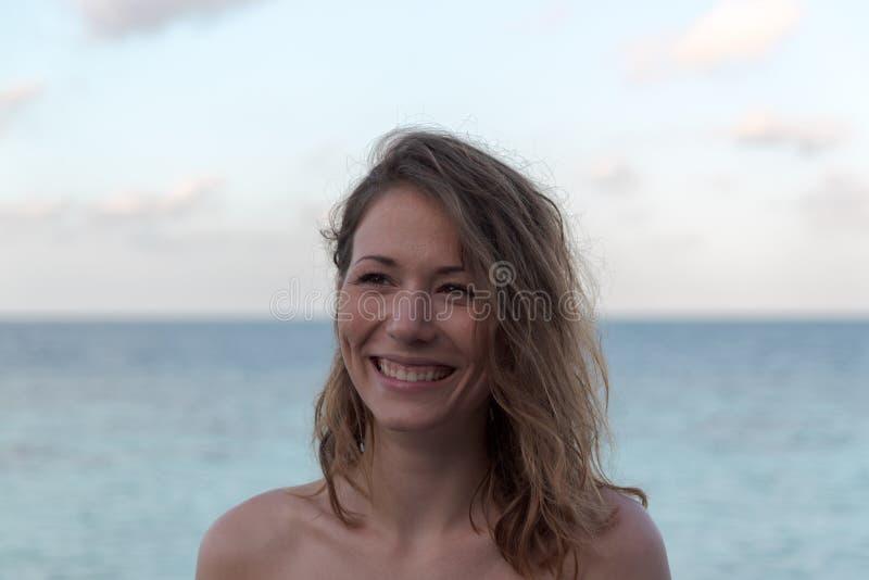 Portret van een jonge gelukkige vrouw in vakantie Overzees als achtergrond stock fotografie