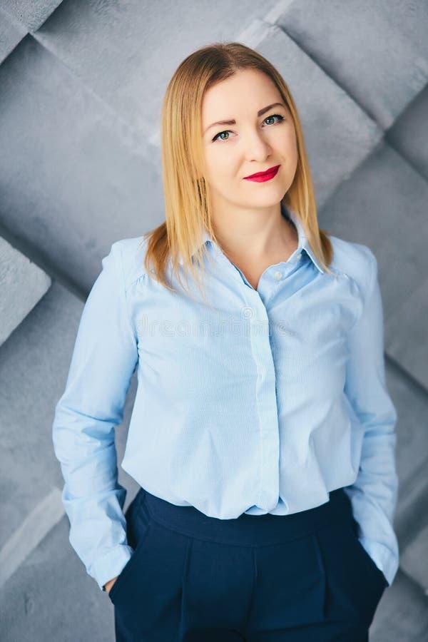 Portret van een jonge glimlachende charmante vrouw in bureaukleren op een grijze muurachtergrond Een mooi blondemeisje in blauw royalty-vrije stock foto's