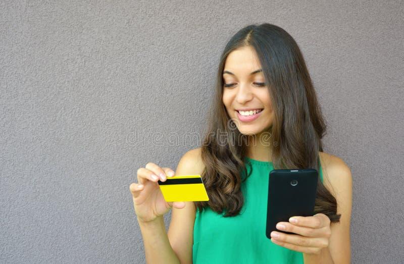Portret van een jonge glimlachende vrouw die online met een smartphone in openlucht kopen stock foto's