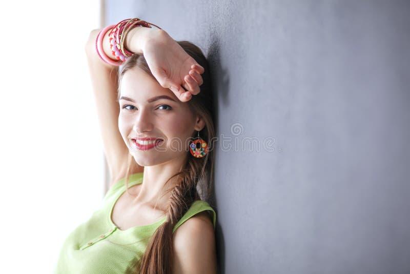 Portret van een jonge glimlachende vrouw op een grijze muurachtergrond stock afbeelding