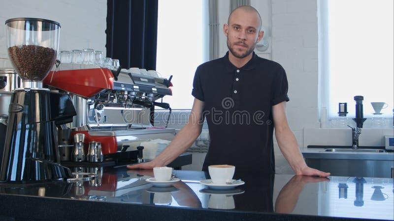 Portret van een jonge het glimlachen mannelijke kop van de baristaholding van koffie bij de koffie royalty-vrije stock fotografie