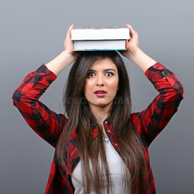 Portret van een jonge holdingsboeken van de studentenvrouw op hoofd tegen grijze achtergrond Vermoeid van het leren van/het bestu royalty-vrije stock foto