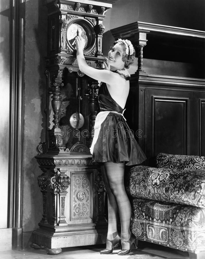 Portret van een jonge housekeeeper het aanpassen tijd op een klok (Alle afgeschilderde personen leven niet langer en geen landgoe royalty-vrije stock fotografie