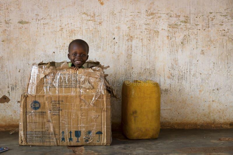 Portret van een jonge jongen die in een kaartdoos spelen in de stad van Nhacra in Guinea-Bissau stock fotografie