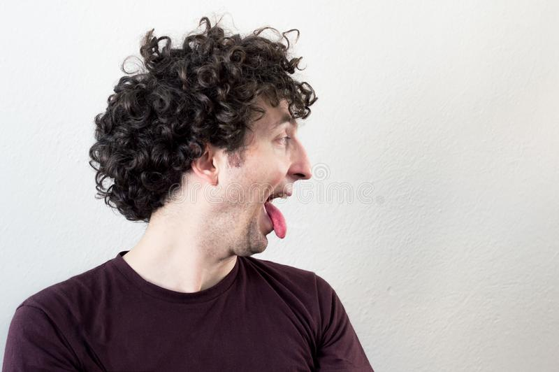 Portret van een jonge, Kaukasische, donkerbruine, krullende haired mens die zijn tong uit op witte achtergrond plakken royalty-vrije stock foto