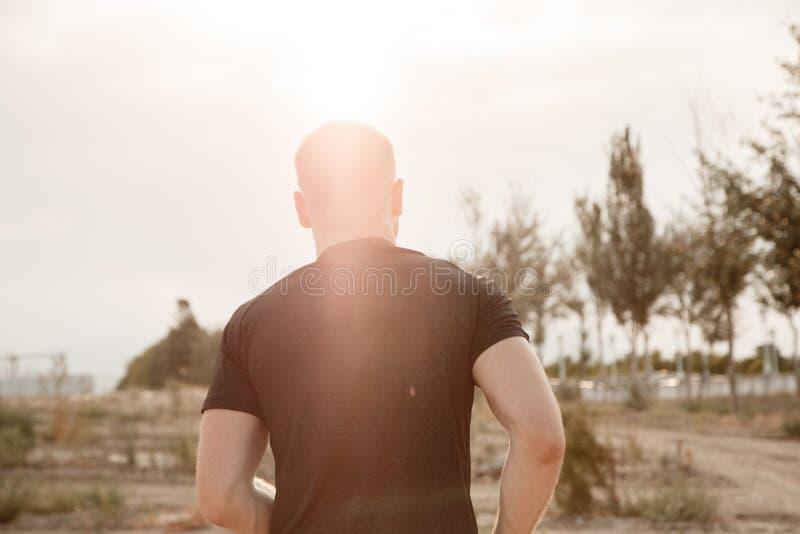 Portret van een jonge Kaukasische kerel in een zwarte t-shirt en zwarte borrels die over ruw terrein tijdens zonsondergang lopen royalty-vrije stock foto