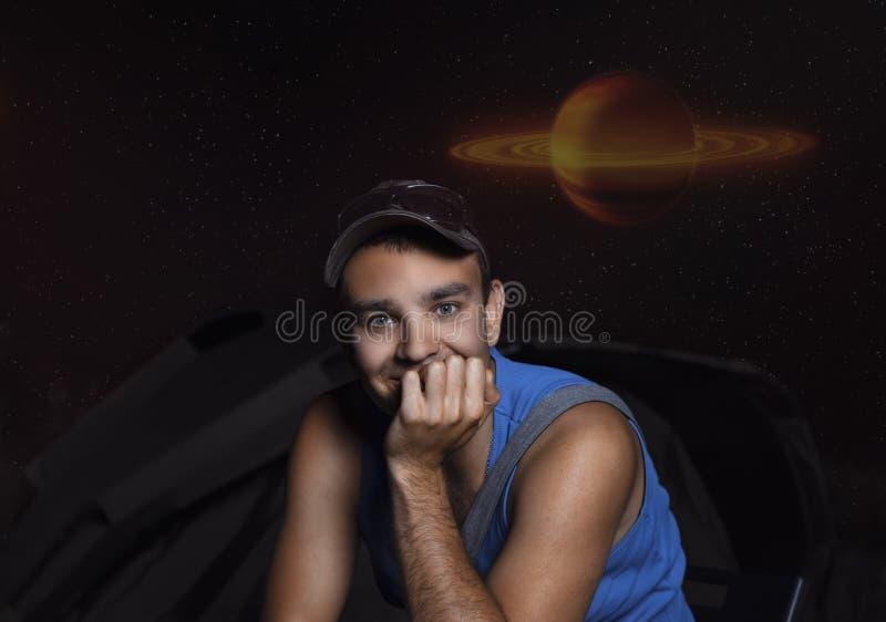 Portret van een jonge kerel bij nacht op een kampeerterrein op een achtergrond van sterren en een rood-gele planeet, abstract bee stock foto's