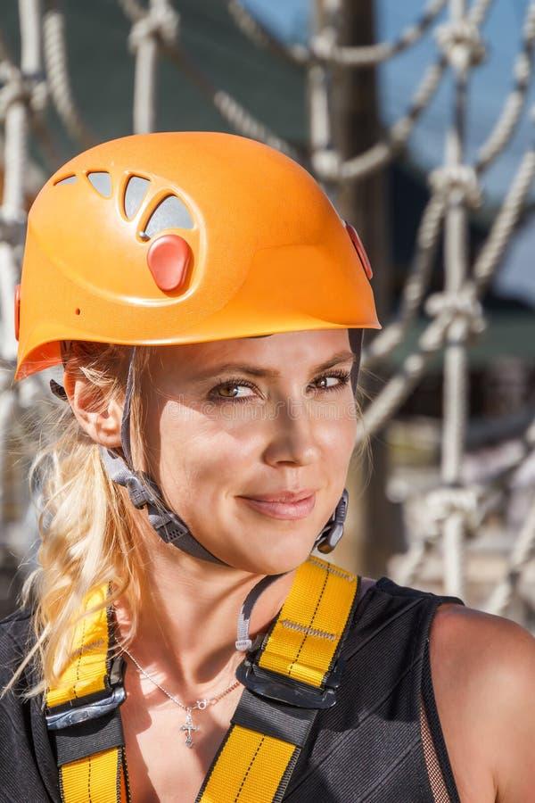 Portret van een jonge klimmervrouw in een beschermende helm tegen de achtergrond van een touwladder in een avontuur die kabelpark stock afbeeldingen
