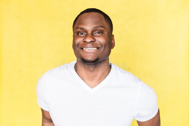 Portret van een jonge knappe glimlachende mens op gele achtergrond stock foto